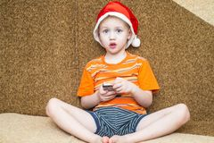 Boy using his smartphone while seated in front of Stock Image