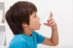 Boy using inhaler. Respiratory system illness Royalty Free Stock Photography