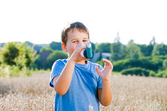 Boy using inhaler for asthma in grain Stock Image
