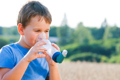 Boy using inhaler for asthma in grain Royalty Free Stock Photography