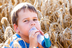 Boy using inhaler for asthma in grain Stock Photography