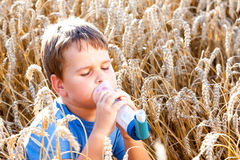 Boy using inhaler for asthma in grain Royalty Free Stock Images