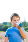 Boy using inhaler for asthma in nature Stock Photo