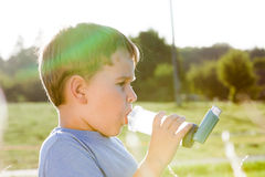 Boy using inhaler for asthma in pasture Royalty Free Stock Photography