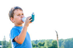 Boy using inhaler for asthma Stock Photo