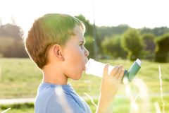 Boy using inhaler for asthma Royalty Free Stock Photography