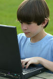 Boy Using Laptop. Boy typing on computer concentrating on his work Royalty Free Stock Image