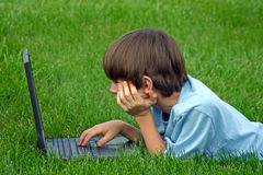 Boy Using Laptop. Boy on computer laying in grass Stock Photo