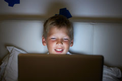 Boy Using Laptop In Bed At Night Stock Photo