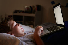Boy Using Laptop In Bed At Night Stock Images