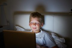 Boy Using Laptop In Bed At Night Royalty Free Stock Images