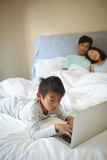 Boy using laptop in bedroom Royalty Free Stock Photography