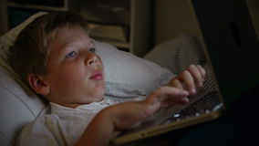 Boy Using Laptop Computer In Bed At Night Stock Photography