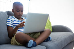 Free Boy Using Laptop While Sitting With Crossed Legged On Sofa At Home Stock Photography - 95870522