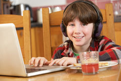 Boy Using Laptop Whilst Eating Breakfast Royalty Free Stock Photos