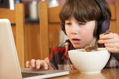 Boy Using Laptop Whilst Eating Breakfast Stock Images