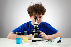 Boy using microscope. Student examining preparation under the microscope Stock Photo