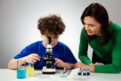 Boy using microscope. Student examining preparation under the microscope Royalty Free Stock Photo