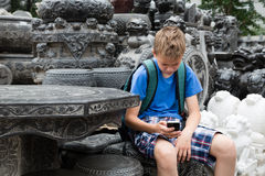 Boy using a mobile the Panjiayuan Antique Market, Beijing Royalty Free Stock Photos