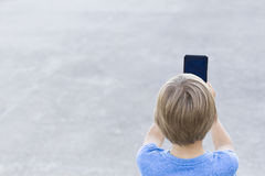 Boy using mobile phone. Child taking photo with his smartphone. Gray urban background. Back view. Technology concept Stock Photography