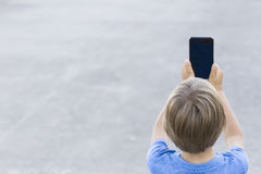 Boy using mobile phone. Child taking photo with his smartphone. Gray urban background. Back view. Technology concept Royalty Free Stock Photography