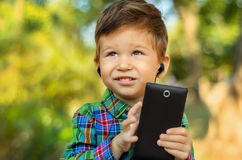 Boy using mobile phone with earphones. Cute little boy using mobile phone with earphones in summer park Royalty Free Stock Images