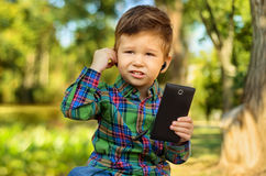 Boy using mobile phone with earphones. Cute little boy using mobile phone with earphones in summer park Royalty Free Stock Image