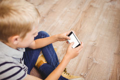 Boy using mobile phone while sitting on hardwood floor. High angle view of boy using mobile phone while sitting on hardwood floor at home Stock Photography