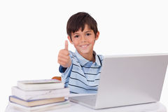 Boy using a notebook with the thumb up. Against a white background Stock Photography
