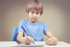 Boy using pen and writing on spiral paper notebook. Boy doing his homework exercises Royalty Free Stock Images