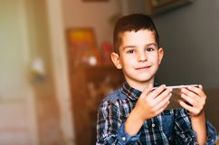 Boy using phone. Happy adorable boy playing with mobile phone stock photos