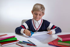 Boy using scissors on the desk Royalty Free Stock Photo