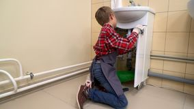 Boy using screwdriver to fix sink. stock video footage