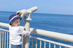 Boy using seaside binoculars Stock Photo