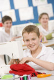 Boy using a sewing machine Royalty Free Stock Image