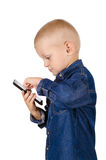 Boy using smartphone. Cute little boy using smartphone in denim blue shirt isolated on white background Royalty Free Stock Photo