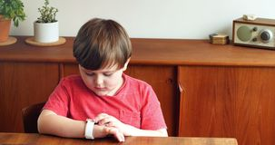 Boy using smartwatch in living room 4k. Boy using smartwatch in living room at home 4k stock video footage