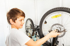 Boy using a spanner while repairing his bicycle Stock Photos