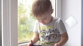 Boy using tablet computer at home on the windowsill stock video footage