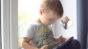 Boy using tablet computer at home on the windowsill stock video