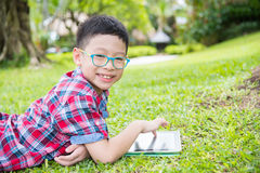 Boy using tablet computer in park Stock Photo