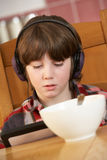 Boy Using Tablet Computer Whilst Eating Breakfast Stock Image
