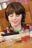 Boy Using Tablet Computer Whilst Eating Breakfast Stock Photos