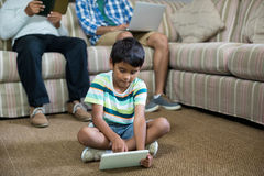 Boy using tablet with father and grandfather in background. Boy using tablet with father and grandfather sitting on sofa in background Royalty Free Stock Photography
