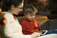 Boy using a tablet with his mother stock photos