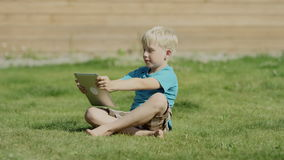 Boy using tablet ipad. Boy using smart phone and smiling lying on grass in a garden stock video footage