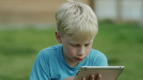 Boy using tablet ipad. Boy using smart phone and smiling lying on grass in a garden stock footage