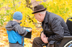 Boy using a tablet pc with grandfather watching Stock Photo