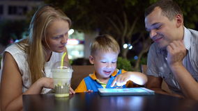 Boy using tablet PC sitting in cafe with parents. Family in cafe in the evening. Son showing something on pad and explaining it to parents, mother having drink stock video footage