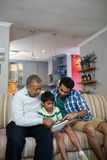 Boy using tablet while sitting with father and grandfather. On sofa in living room at home Stock Photography